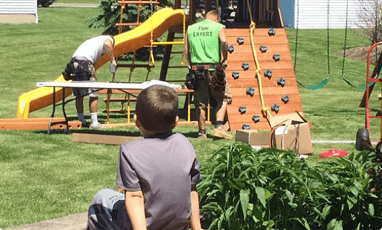 Boy watching playset installed